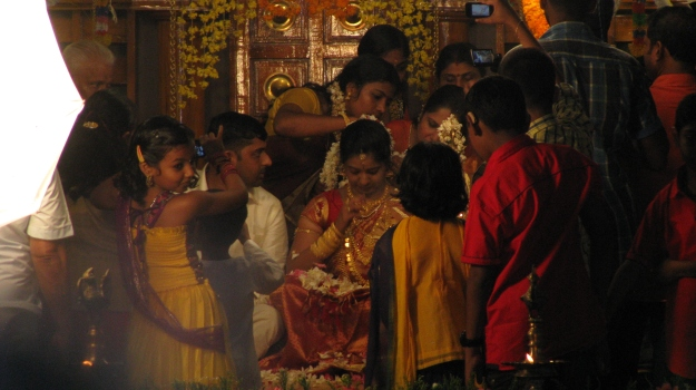 A Hindu wedding as glimpsed through a horde photographers and other relatives.